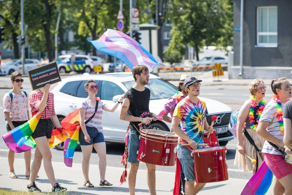 Grupo de personas marchando y tocando instrumentos de percusión con banderas LGTBI+